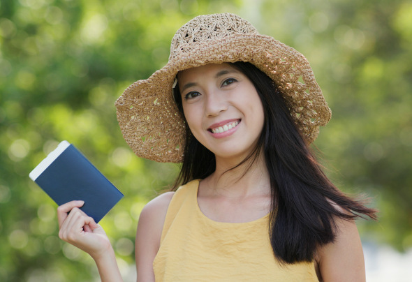 Happy woman hold passport and smiling at outdoor