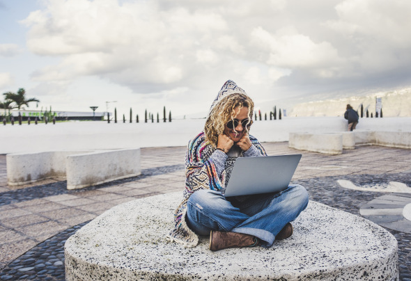 Happy and free digital nomad alternative woman working with technology everywhere in the world traveling a lot - travel lifestyle with laptop computer modern job - people connected outdoor
